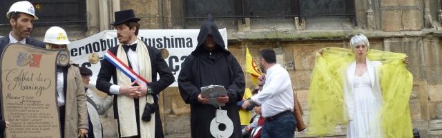 Photo d'une scène réalisée par les manifestants anti-nuclaires ce 26 avril 2014 à Paris, au sortir de la rue Beaubourg, où l'interview de Mélisande Seyzériat a eu lieu, au pied de l'Eglise Saint Merry, face à la célèbre fontaine Stravinsky. Il s'agit de la célébration, parodique, du mariage des élus français avec l'énergie nucléaire, représentée par une femme, impassible et muette, vêtue de blanc, et arborant un voile jaune imprimé du motif de risque d'exposition à des rayonnements ionisants. Le contrat de mariage est tenu par un représentant d'EDF. C'est la Mort, tenant une paire de menottes, qui officie à la cérémonie de mariage. Crédit photo B.Brochenin.